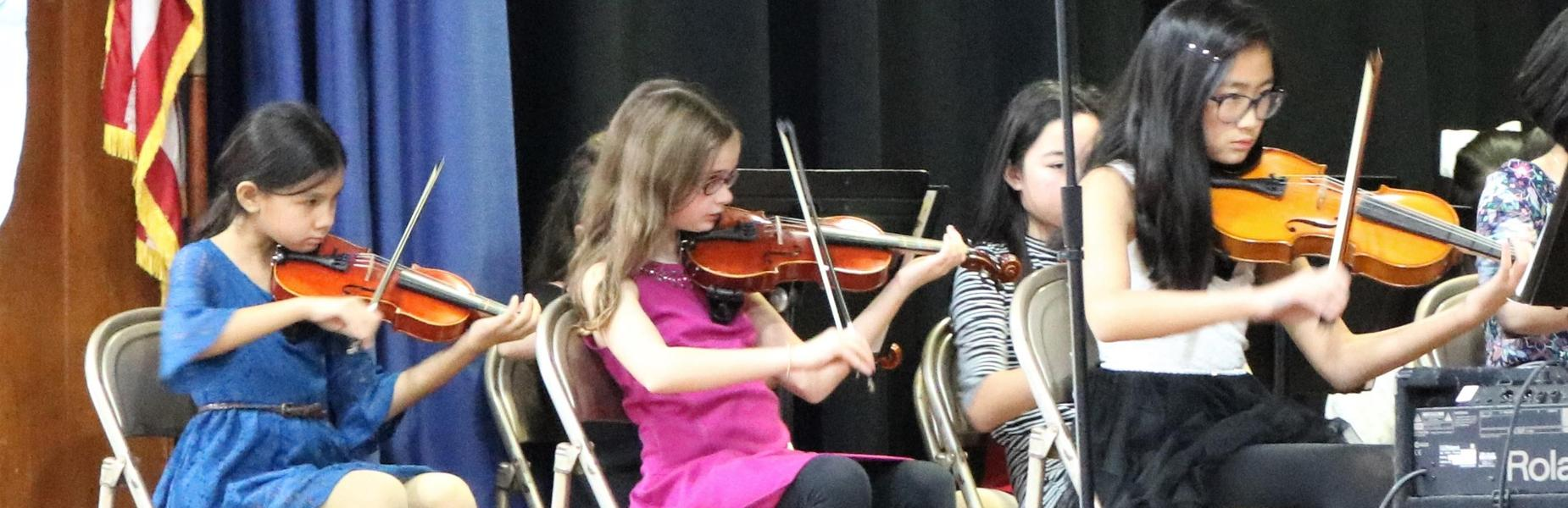 Elementary students perform holiday String Concert at Tamaques School in December 2018.  Pictured here are three young violinists.