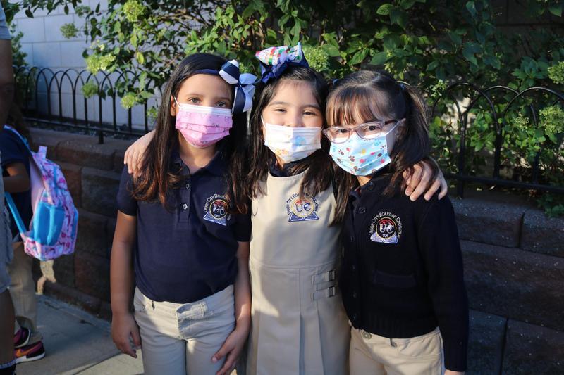 3 girls posing together in masks