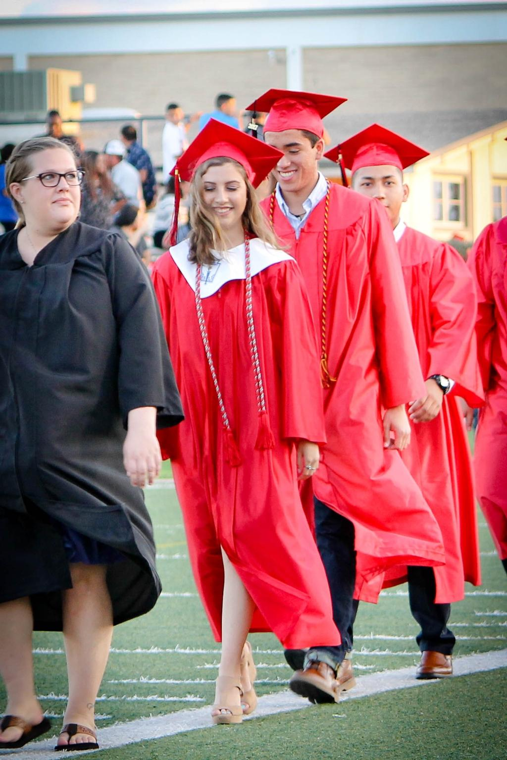 students of the victoria east high school 2018 graduating walking into memorial stadium, smiling female and male student