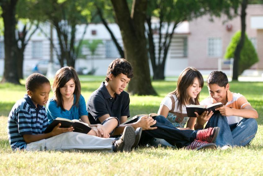 kids sitting in grass reading