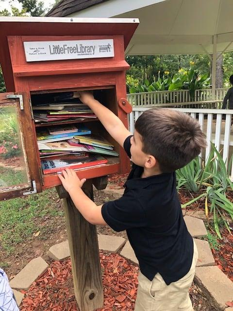 student stocking a free library