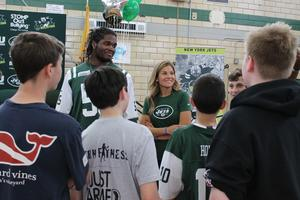New York Jets linebacker Lorenzo Mauldin talks with students and Edison Intermediate School health/physical education teacher Christine Cabrales after an anti-bullying assembly organized by Cabrales.