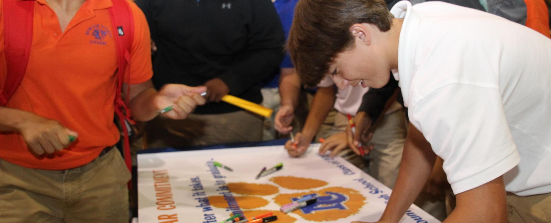Student signing a poster