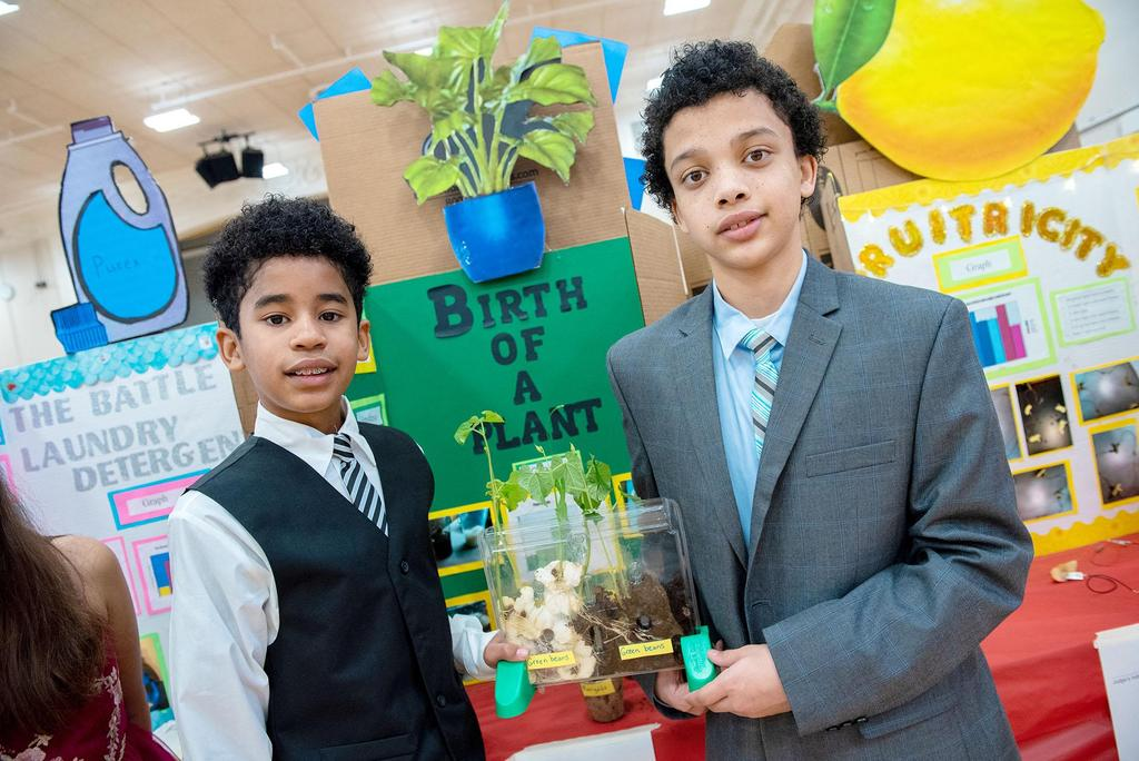Two students stand in front of their project called The Birth of a Plant