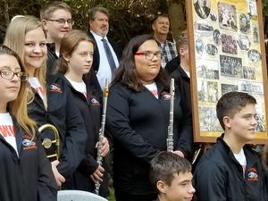Seth Principal and WV band pose with a poster of Mr. Woodard