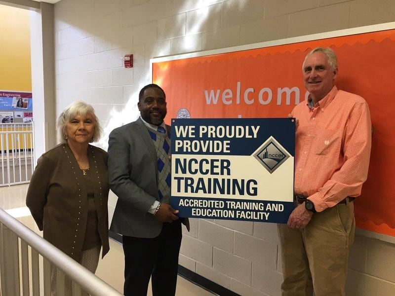 Dr. Pilot, Mr. Johnson, and Ms. Clarkson standing with the new NCCER sign .