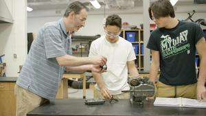 teachers helps students with machine project on table