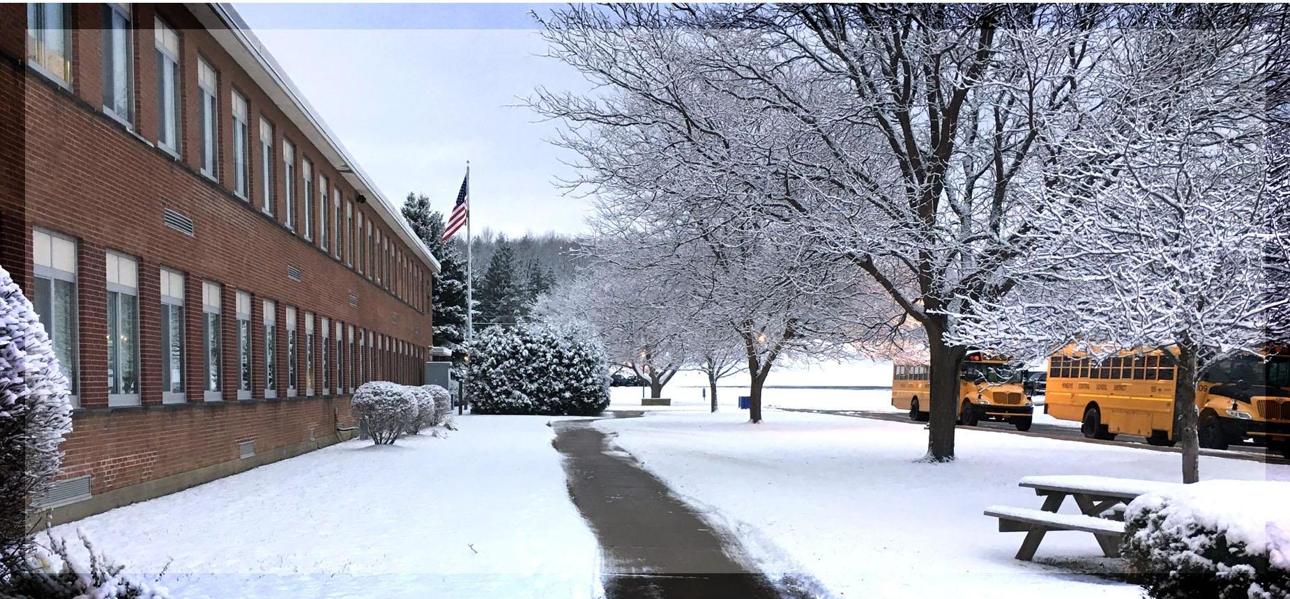 Photograph of the school and buses in the midst of snow.