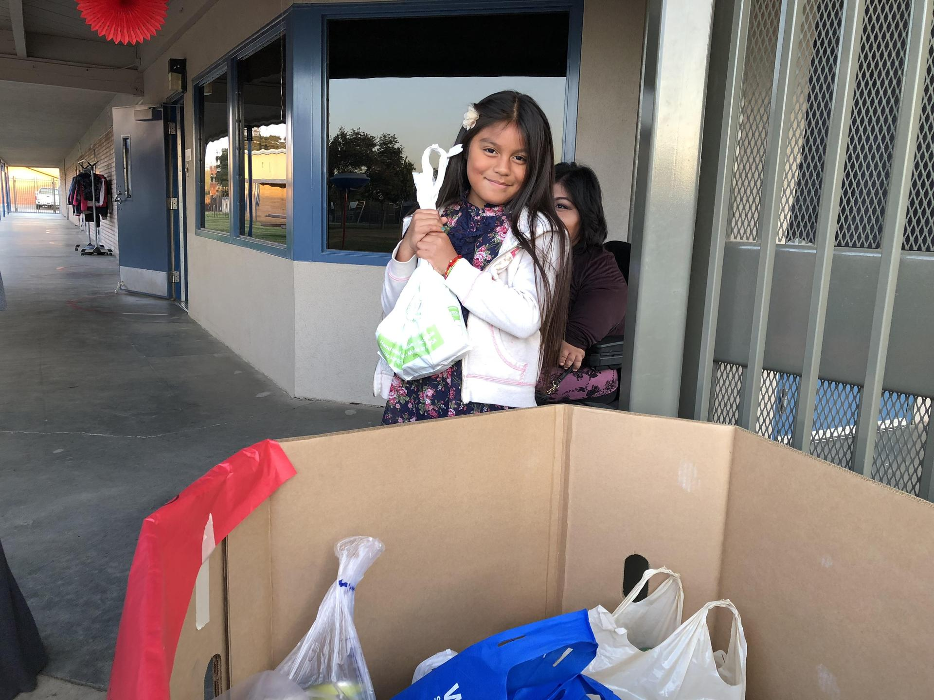 A student donating canned foods at movie night.