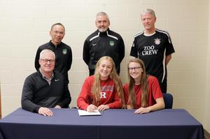 Regan Berg with her dad, friend and club coaches at her signing
