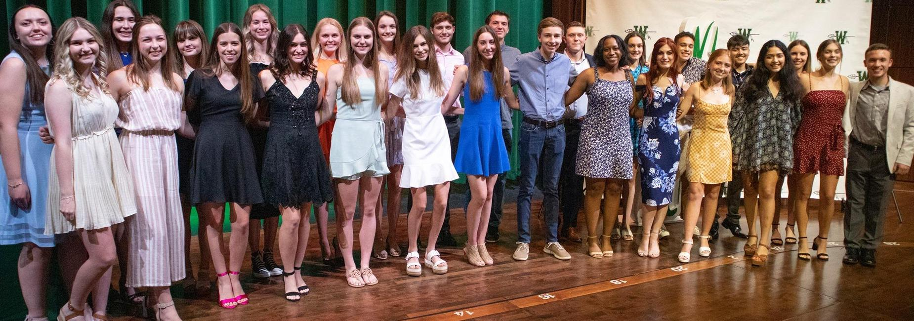 group of 24 girls & 6 boys pose together on stage