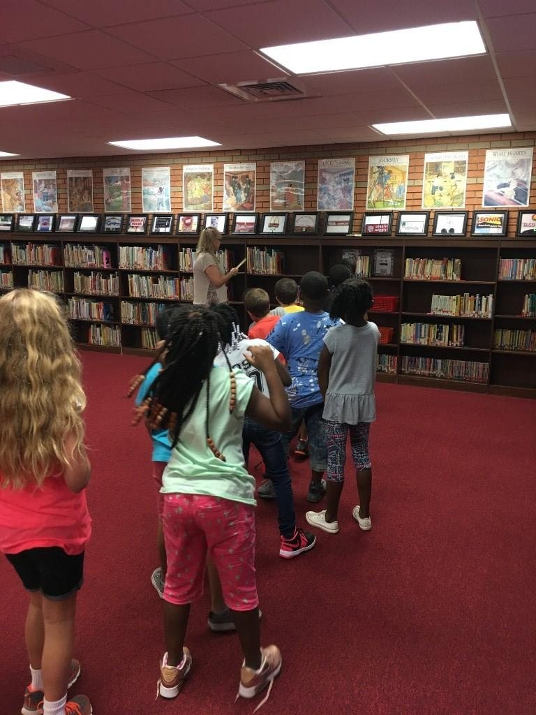 Mrs. Haney showing them how to find a book.