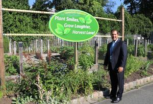 Tamaques principal David Duelks poses with the new sign provided by the PTO for the Tamaques Garden.