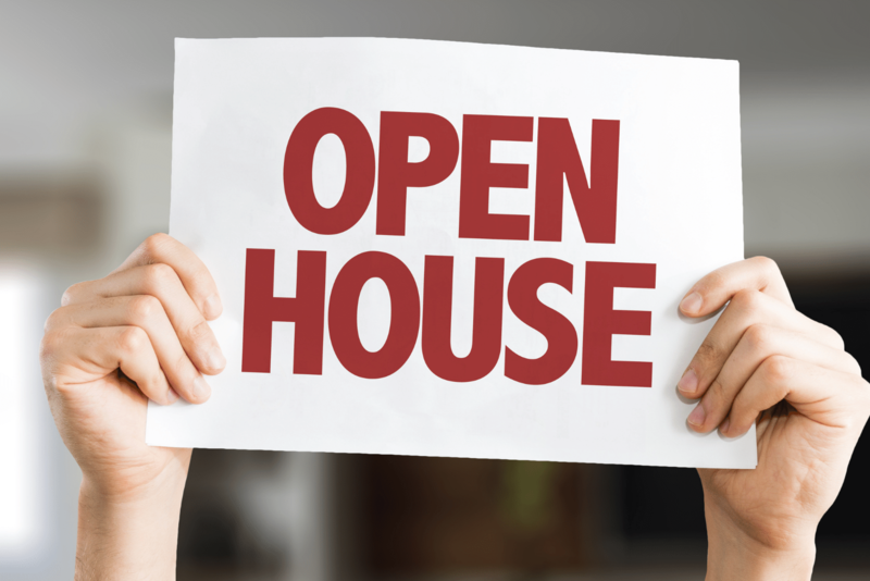man's arms hold up sign that says open house with the background bokehed out