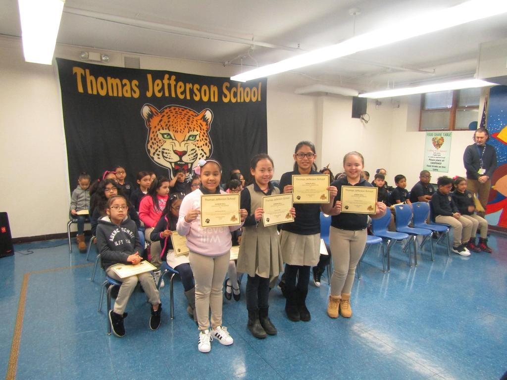 four girls showing off their honor roll certificates