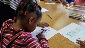 Female Head Start preschool student practices writing her name