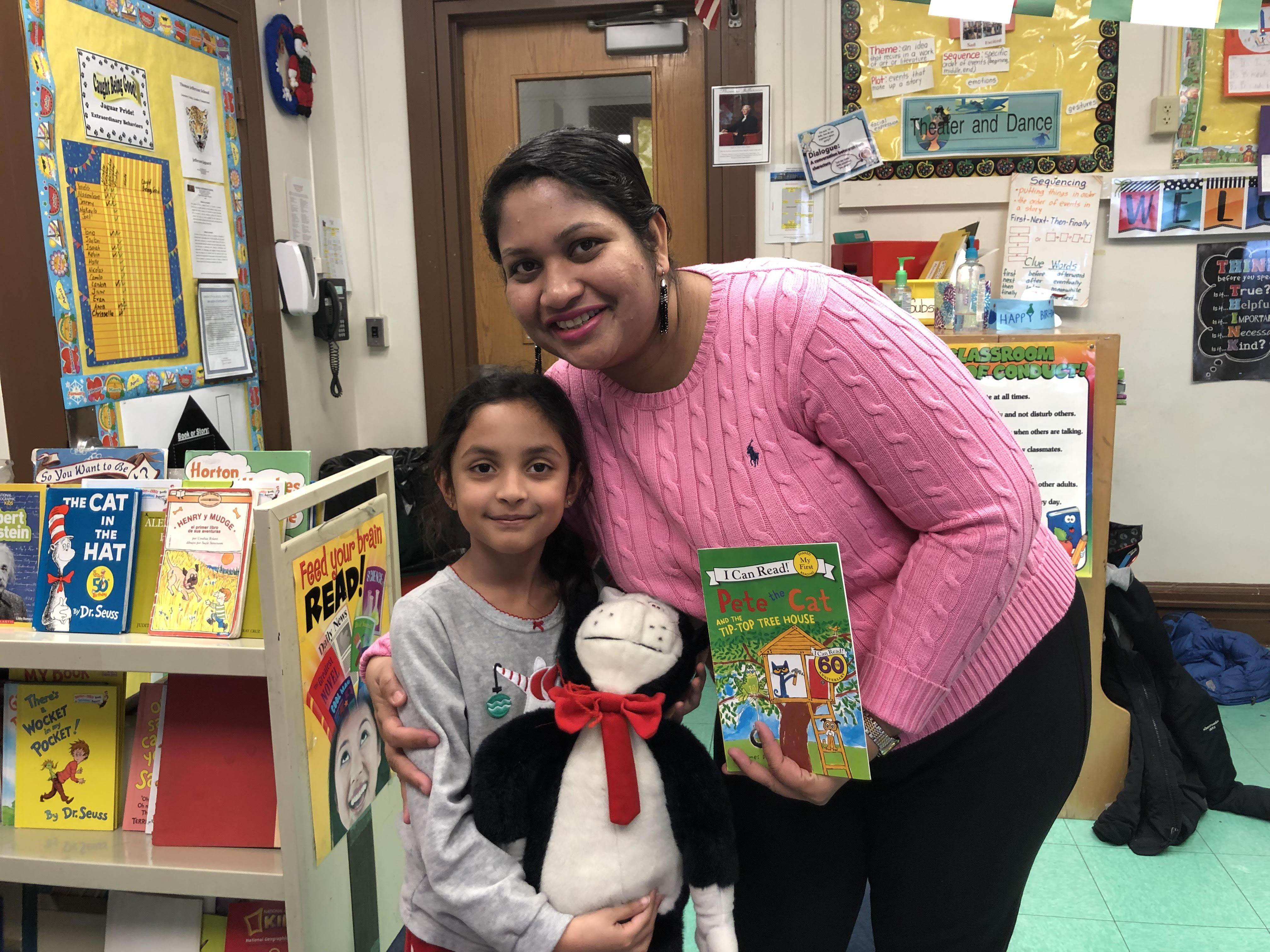 mother holding daughter who is holding a cat in the hat doll and book