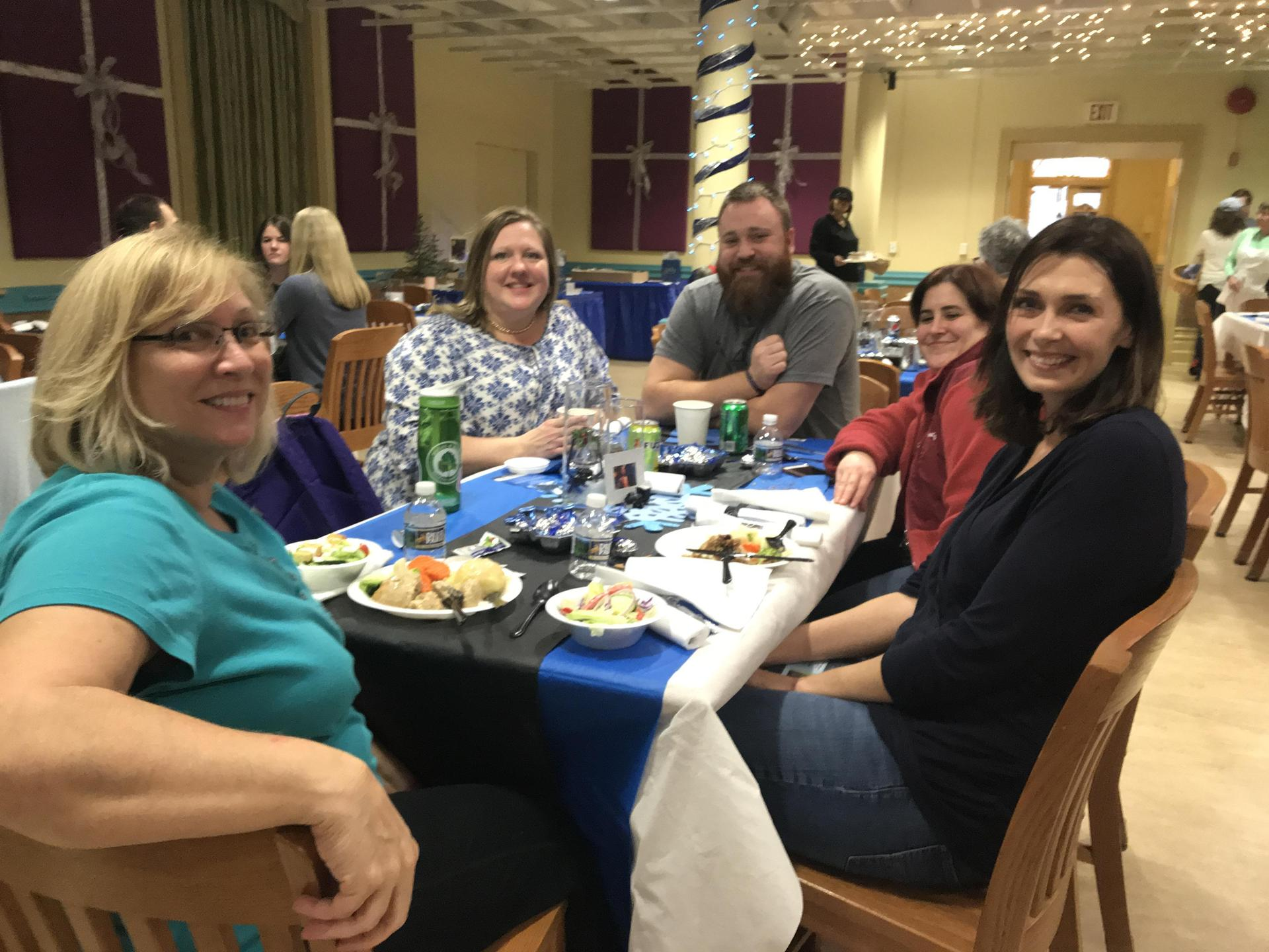 five staff members sit at a table enjoying a holiday meal