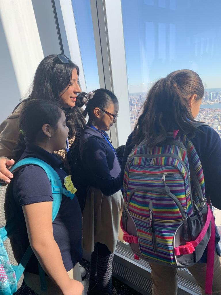 Ms. Logothetis standing with several students looking down on NYC
