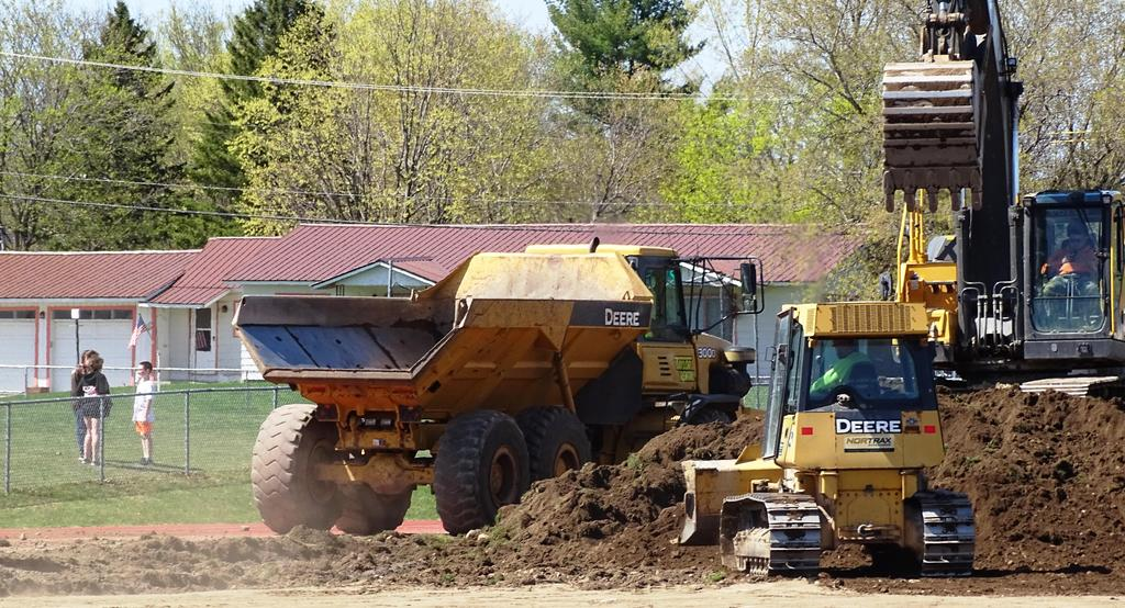 A May 2019 component of constructing a comprehensively improved feature field and all-weather track was removing the legacy track that served the school community for many years. Pictured here are some of the earth moving equipment operated by members of J E Sheehan's site construction crew.
