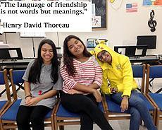 """The language of friendship is not words but meanings"" - Henry David Thoreau  Image of 3 girls sitting in music class with broad smiles"