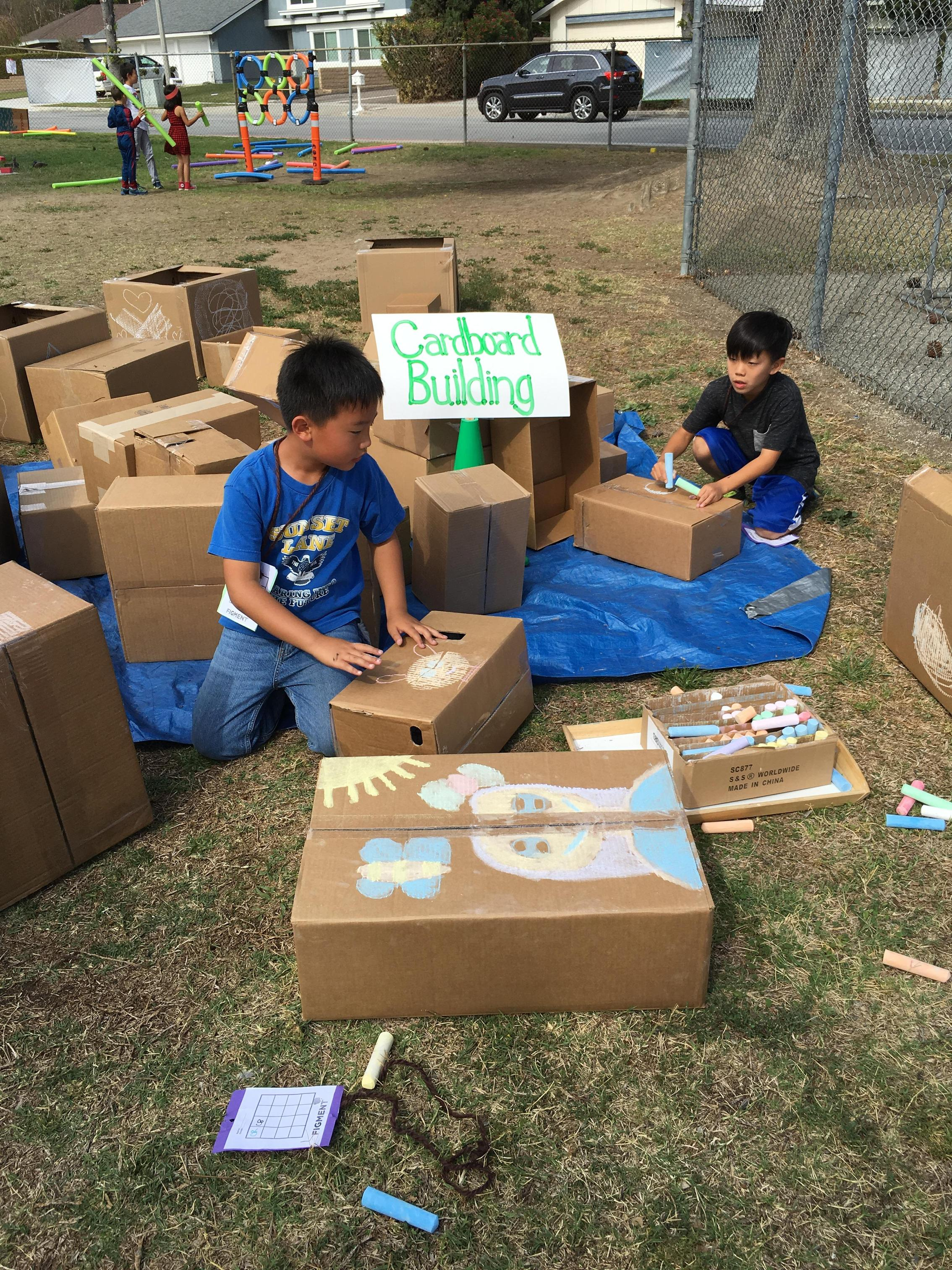 Two children building with cardboard boxes