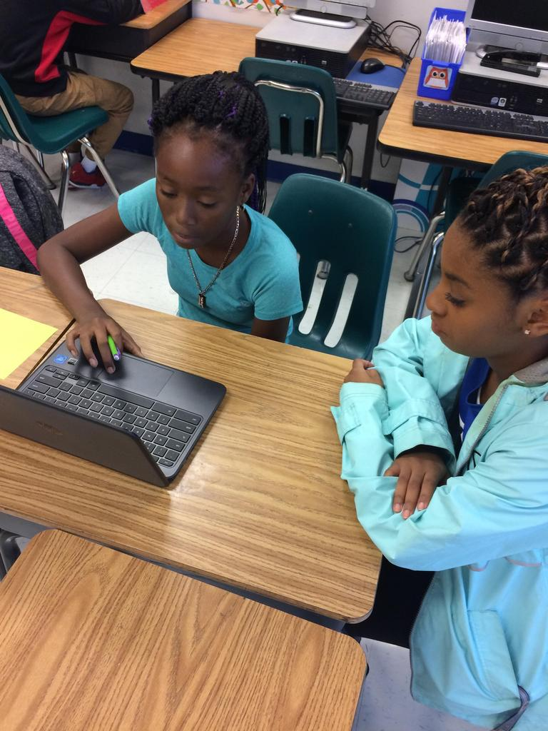Barton College student looks on with a fifth grader, while the fifth grader works on the chrome book.