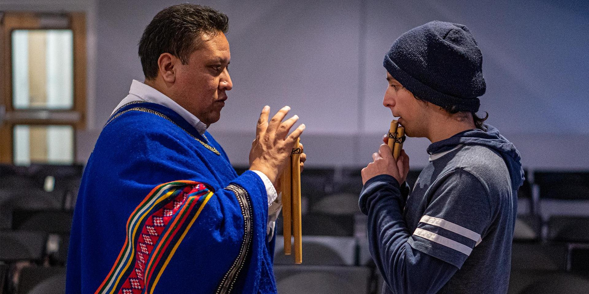 New Inca Son band leader teaching a student to play the pan flute.