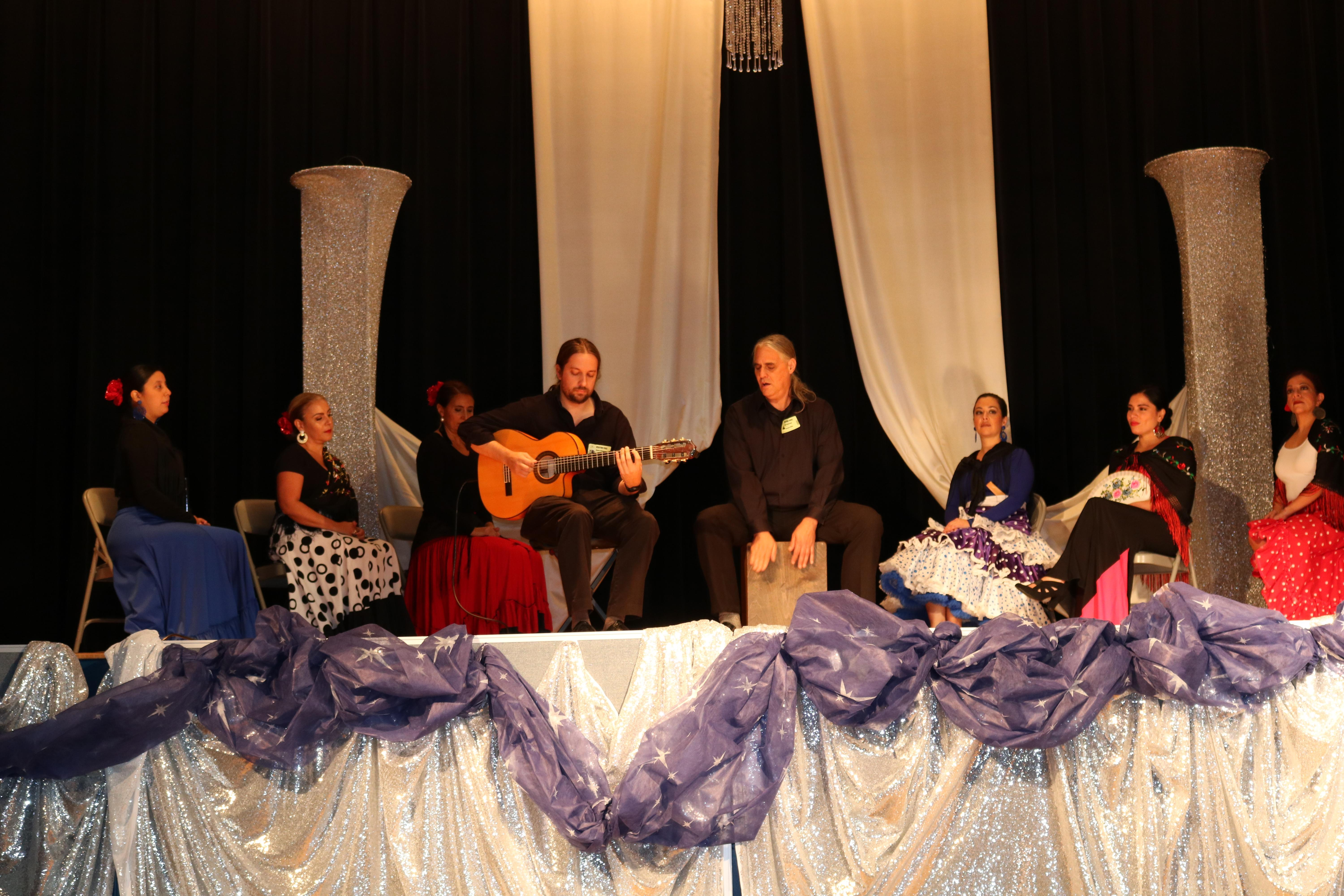 CP teachers in flamenco costumes accompanying two musicians one with a guitar and the other the mambo drum