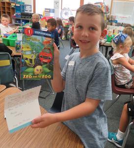 Donovan Matthes, a first grader in Karen Seifert's class, shows the book and note he received.