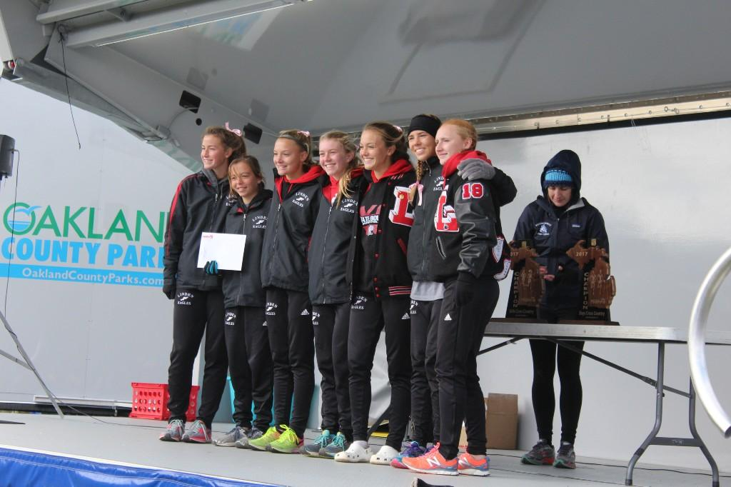 Female cross country runners on an awards podium