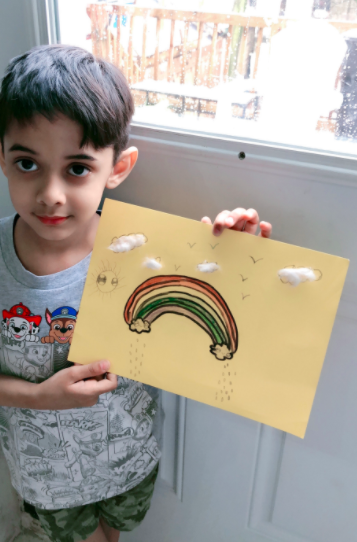 Boy holding rainbow drawing with cotton ball clouds