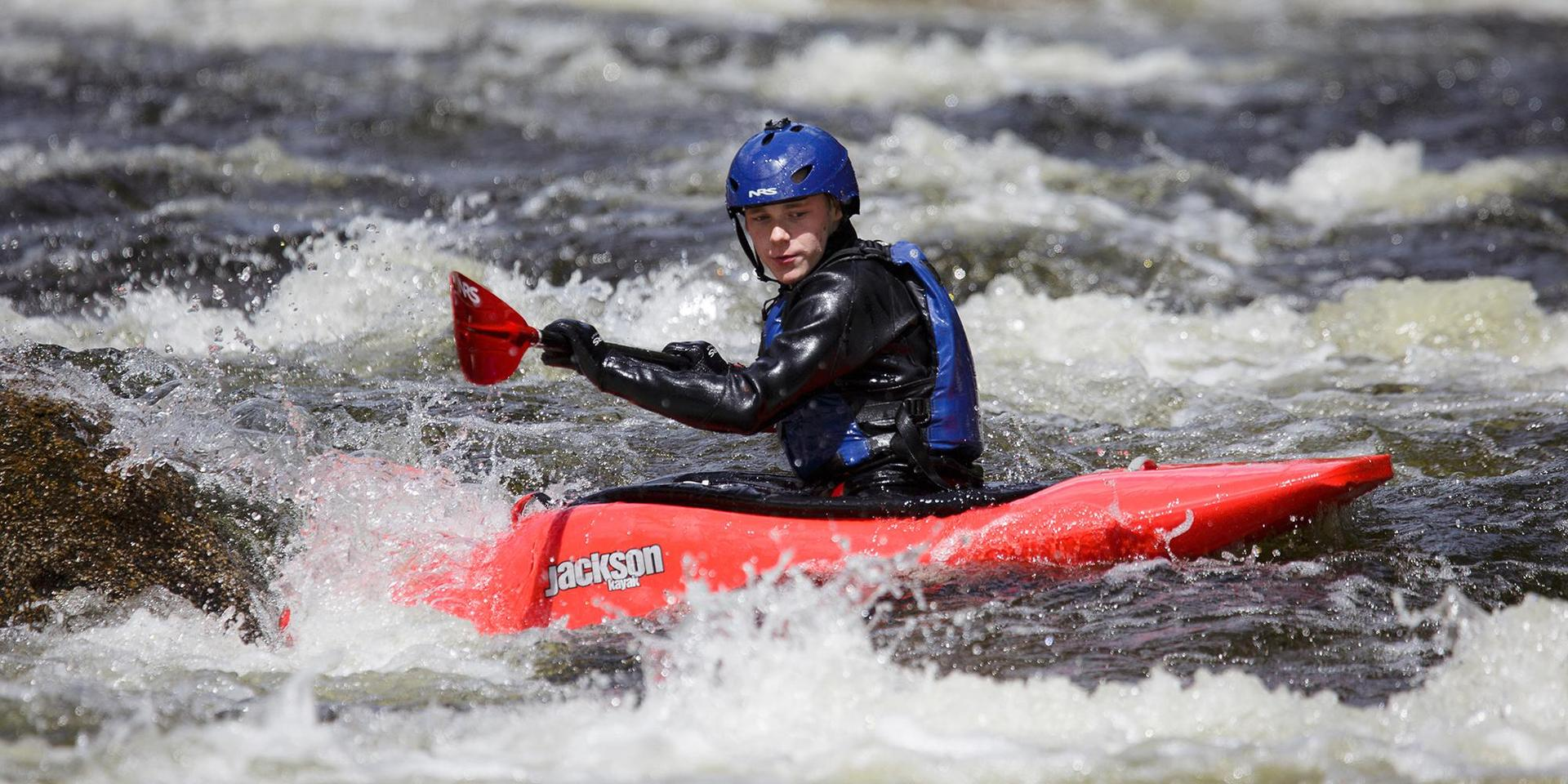 A student whitewater kayaking.