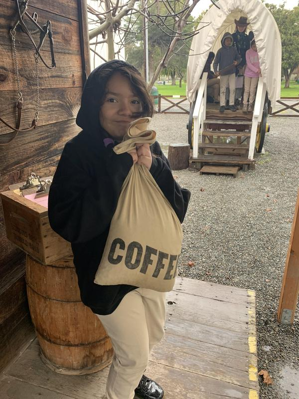 student posing with the bag of coffee she is loading in the wagon