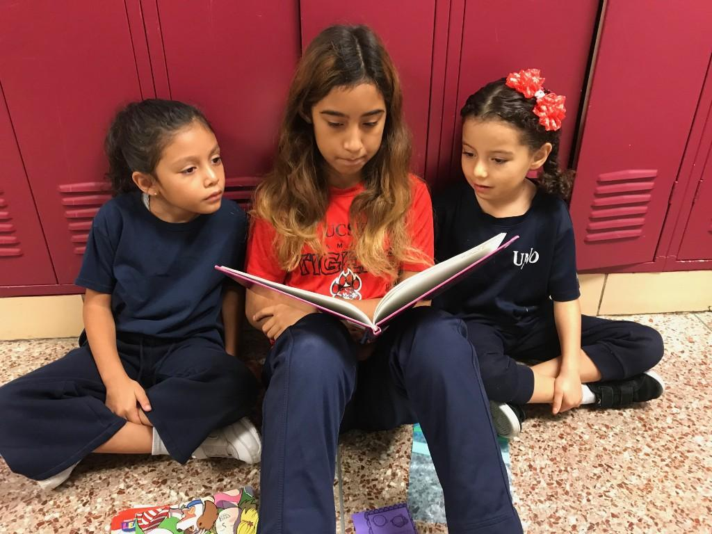 Two younger students partner read with an older student