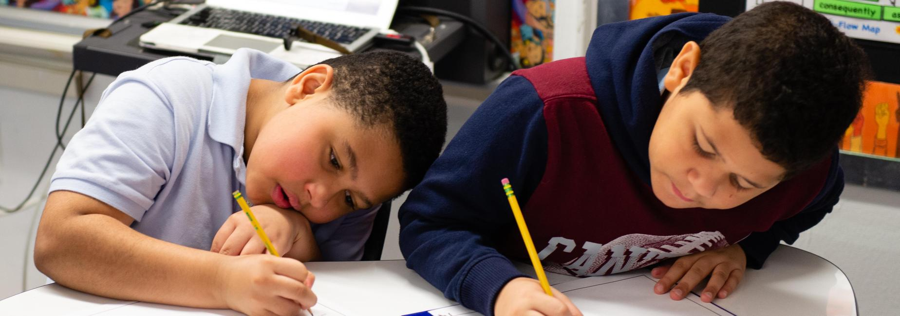 Two elementary school students leaning against a table and writing.