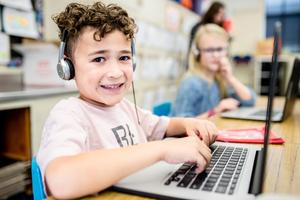 Student posing for a picture while using a Chromebook and with headphones on.
