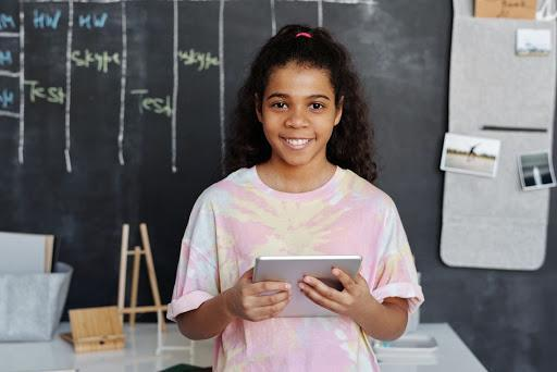 Student holding ipad standing in front of chalkboard.