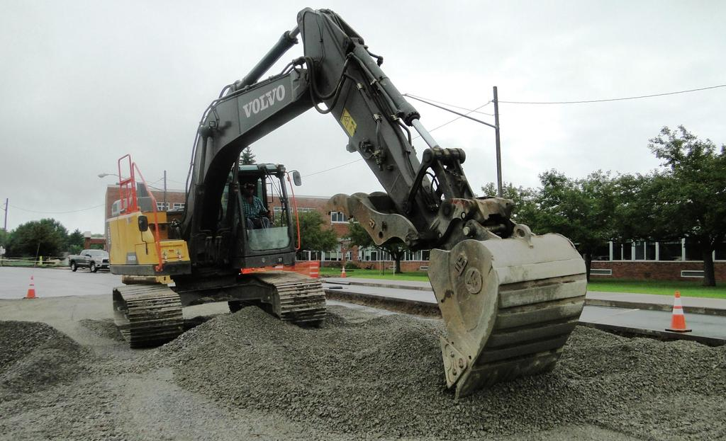 A large tracked excavator moves stone as part of re-constructing the main campus bus loop August 14, 2018