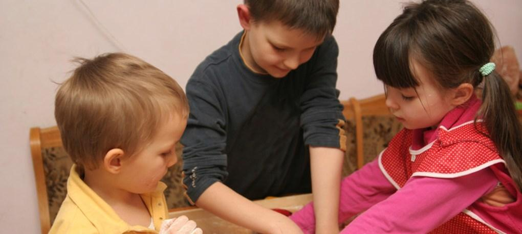 Three children doing artwork at a table.