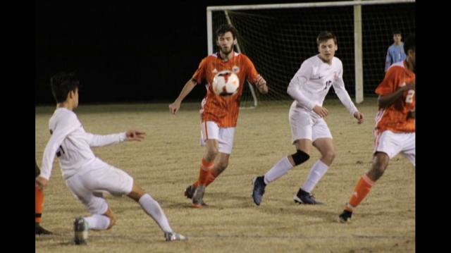 Dylan L. kicking the soccer ball.