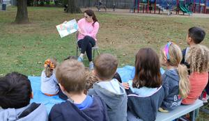 Photo of PTO mom reading to kindergarten class at annual Pumpkin Patch.