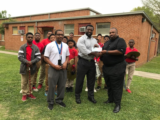 A photo of Baker Middle principal, band director and students presenting Baker High Band director with a check to help fund their trip to perform at Carnegie Hall in New York