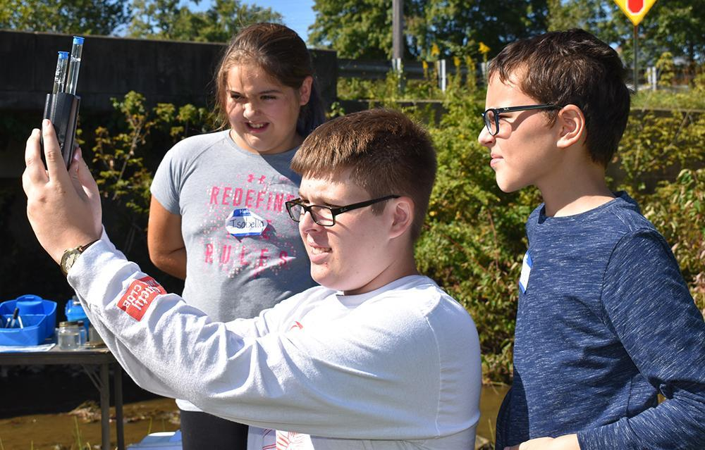 students conducting chemical tests on stream water