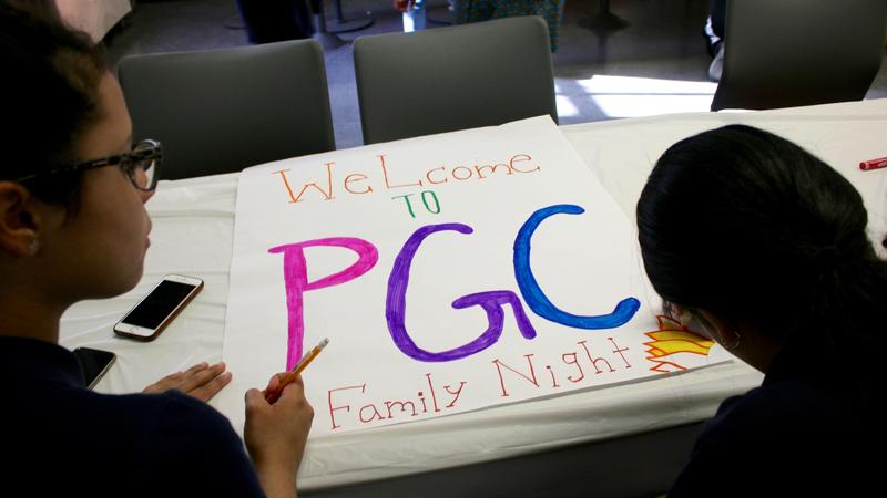Two girls making a Family Night poster.