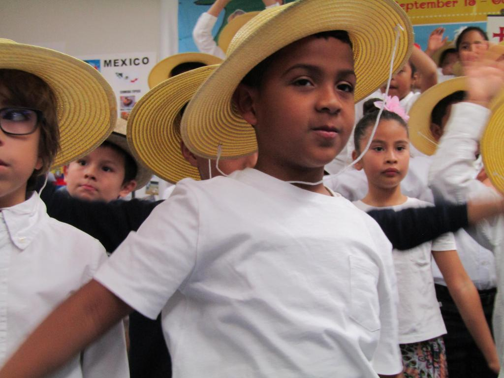 close up of a boy wearing a straw hat performing on stage