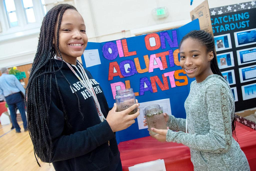 Two students hold jars filled with liquids as they stand in front of their project