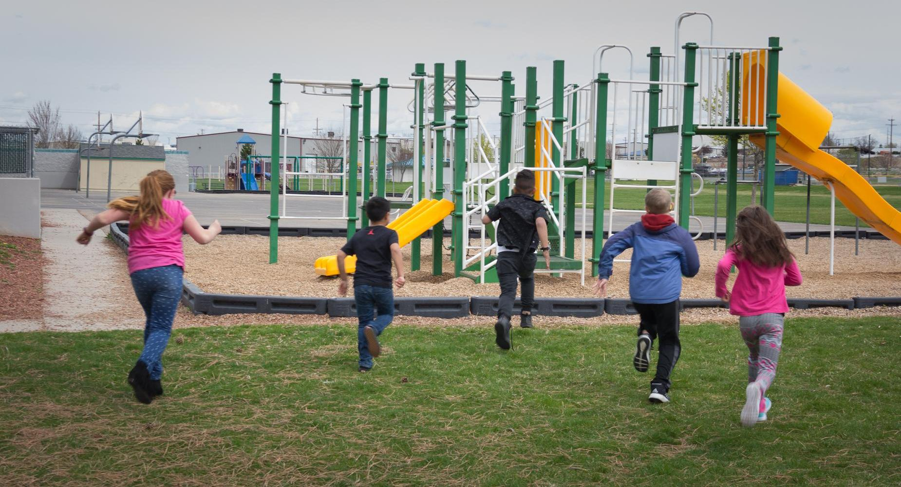 Five children run toward the playground