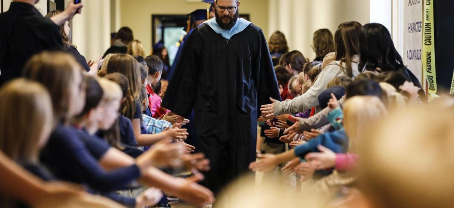 Mr. Collins leading 2019 graduates down the hallway to the commencement ceremony
