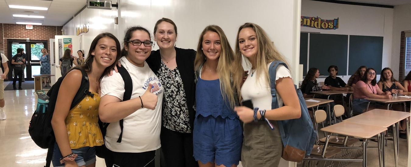 Ms Kincaid smiling with four of her students in 300 hallway